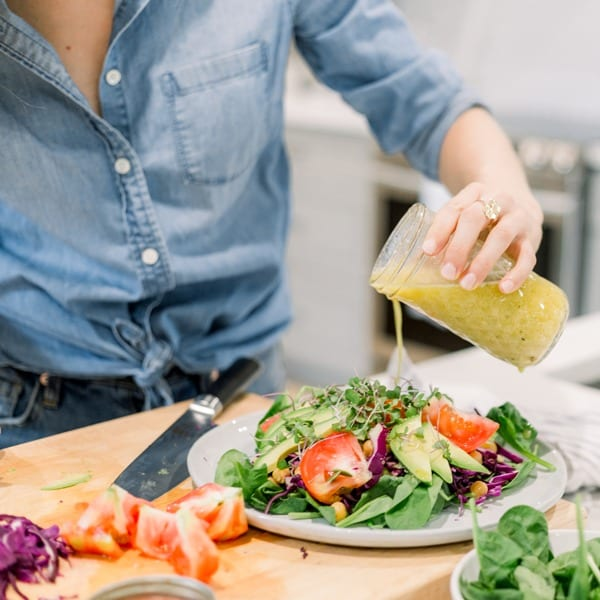 carly paige of fitliving eats pouring salad dressing on salad
